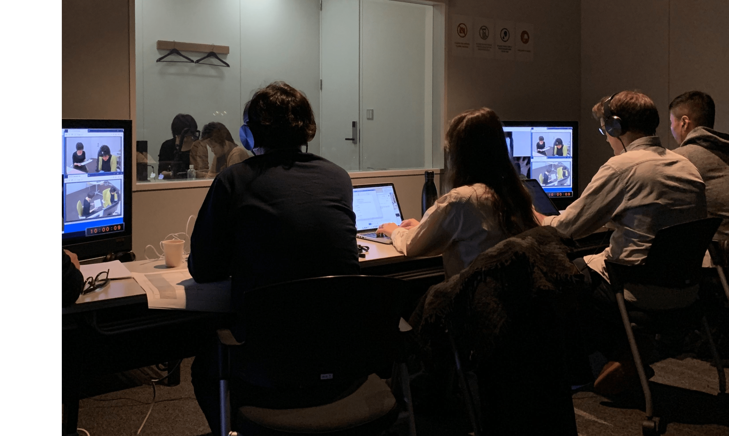 A group of people sitting at a desk in front of a computer