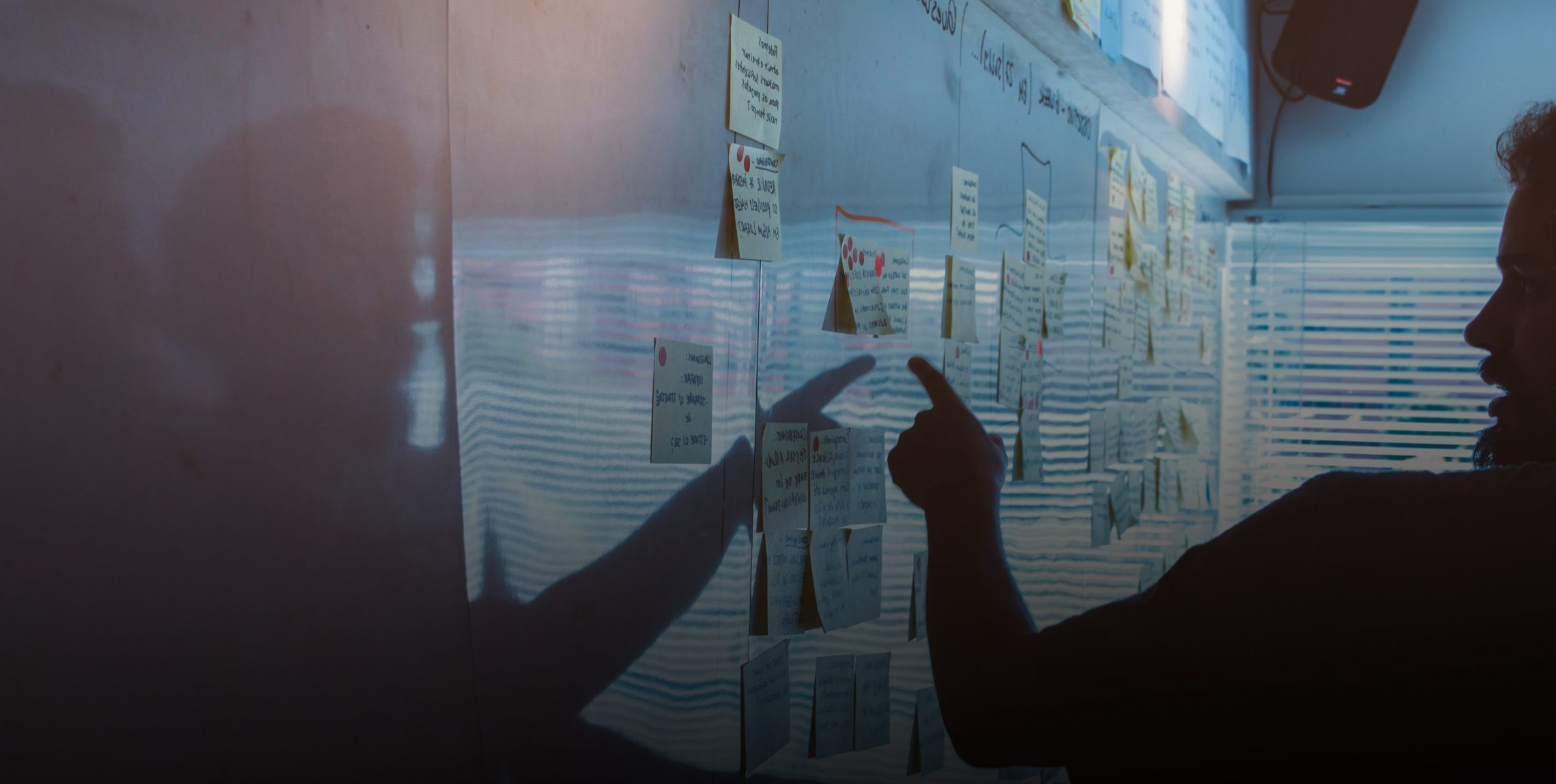 UX Designer placing post-it notes on a whiteboard