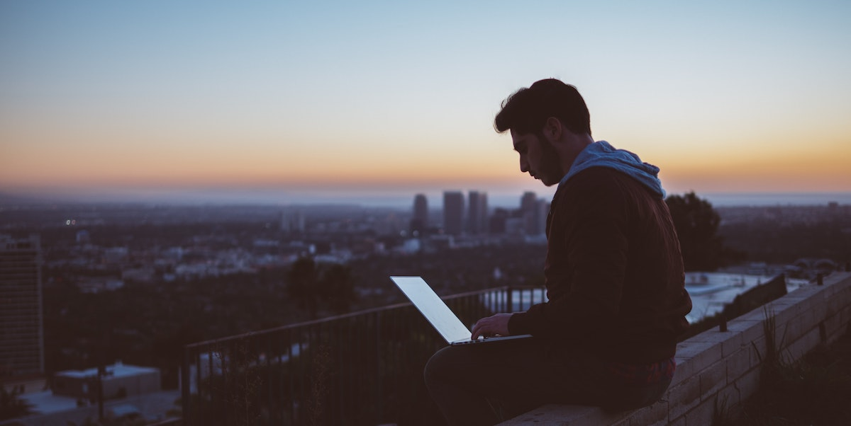 Gig worker at computer overlooking cityscape at sunset