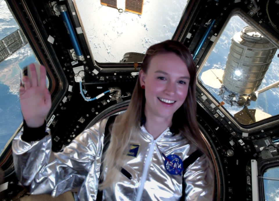 A screenshot of Shawna on zoom dressed as an astronaut with a spaceship background